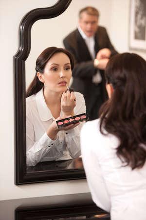 hurry up: Per favore, sbrigati! Fiducioso donna di mezza et� facendo il make-up, mentre il marito puntando i suoi orologi e guardando arrabbiato