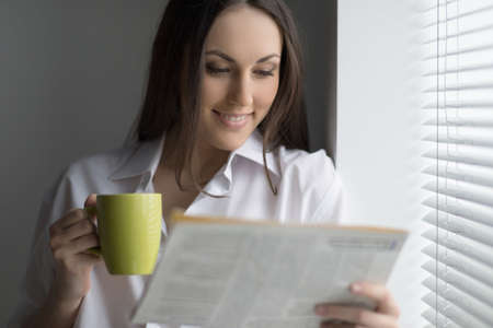 fresh news: Hot coffee and fresh news. Beautiful young woman reading newspaper and drinking coffee Stock Photo
