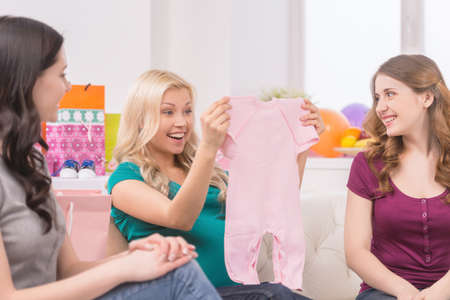 Baby shower. Beautiful pregnant woman receiving gifts from her friends photo