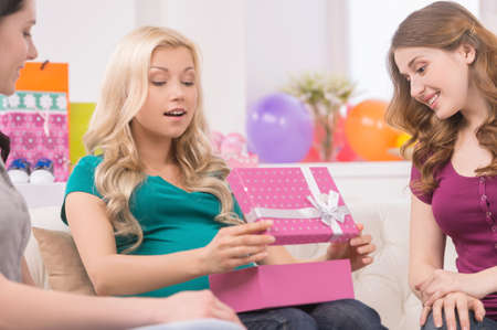 baby open present: Pregnant woman on baby shower. Beautiful pregnant woman receiving gifts from her friends Stock Photo