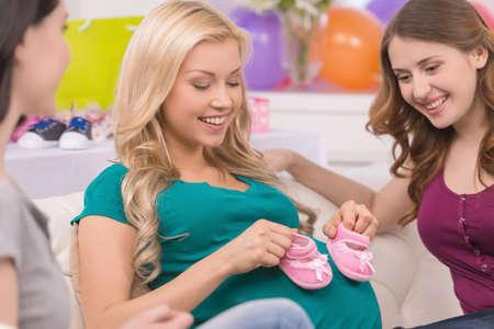 mujer bonita: Las mujeres j�venes en la ducha del beb�. Hermosa mujer embarazada mostrando botines a sus amigos