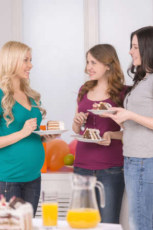 baby shower party: Baby Shower party. Cheerful young pregnant woman talking to her friends and eating cake