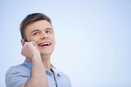 On the phone. Cheerful young man talking on the mobile phone and smiling Stock Photo