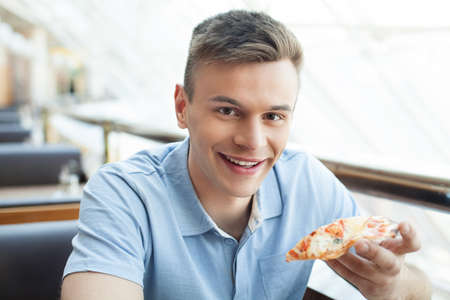 only man: Man eating pizza. Cheerful young man eating pizza at the restaurant