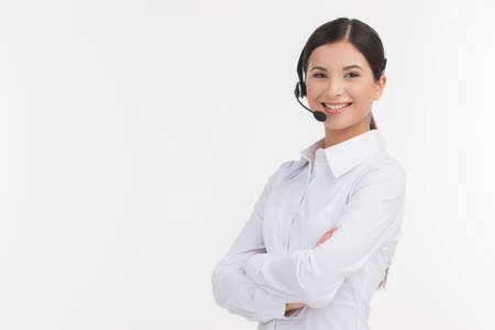 customer service representative: Confident customer service representative. Beautiful young female customer service representative in headset holding her arms crossed and looking at camera while isolated on white