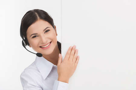 Cheerful customer service representative. Cheerful young female customer service representative in headset looking out of the poster while isolated on white