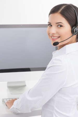représentant du service à la clientèle au travail. Vue arrière de la belle jeune femme représentant du service à la clientèle dans l'écouteur travaillant sur l'ordinateur et regarder par-dessus l'épaule tout en isolé sur blanc