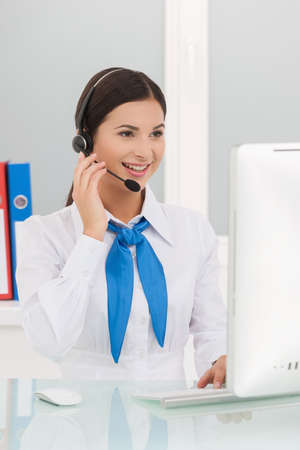 Beautiful customer service representative. Cheerful young female customer service representatives in headset working at the computer and smiling photo