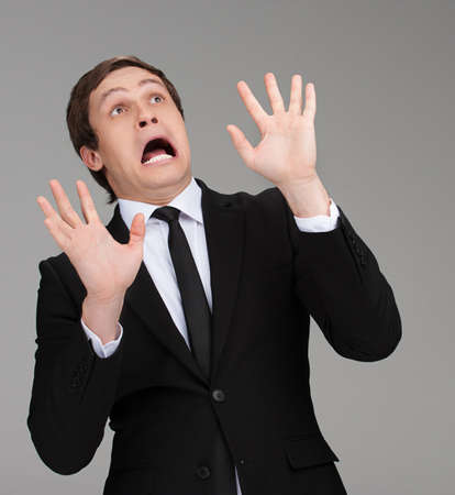 terrified: Scared businessman. Terrified young businessman looking up and gesturing while isolated on grey Stock Photo
