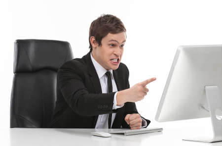 Troubles at work. Furious young businessman pointing computer monitor while sitting at his working place Stock Photo - 23423565