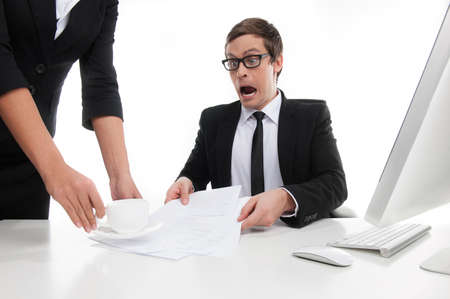 What are you doing? Stressed young businessman shouting at his secretary putting a cup of coffee on the documents photo