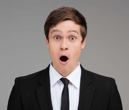 Shocked businessman. Portrait of surprised young businessman looking at camera and keeping his mouth open while isolated on grey photo