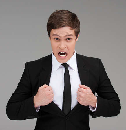 grabbing hand: Furious man. Furious young businessman with open mouth grabbing his suit with both hands and looking at camera while isolated on grey