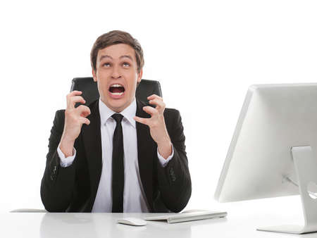 working place: Oh no! Furious young businessman gesturing while sitting at his working place