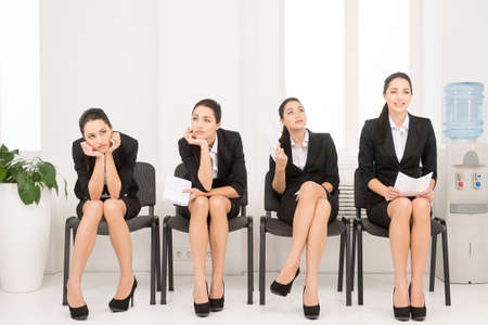インタビューを待っている一人の女性の 4 つの異なるポーズ。オフィスの椅子の上に座っています。