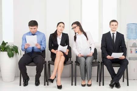 papeles oficina: Cuatro personas esperando para la entrevista. Mirando nervioso Foto de archivo