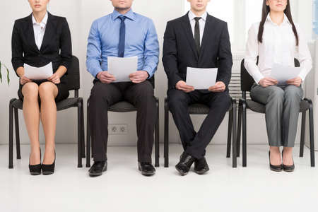 people at work: Four candidates competing for one position. Having CV in his hand Stock Photo