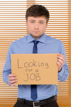 employment issues: Sad unemployed man is looking for a job. Showing plate with sign