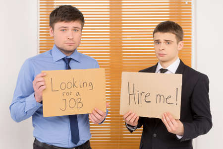 unemployed: Two unemployed men looking for a job.  Showing plates with sing asking for vacant position