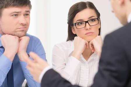 Twee mensen luisteren man. Vrouw met aandacht en man met verveeld gezicht.