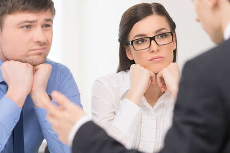 Two people listening to man. Woman with attention and man with bored face. photo