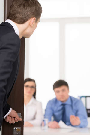 Worried man entering a room for job interview. Two Human Recourses Agent sitting in office. Blur background