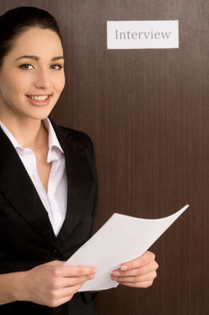 Smiling confident woman standing with CV. Getting ready for interview photo