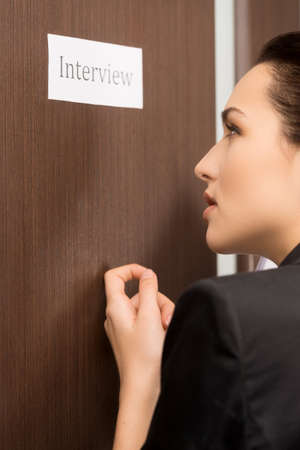 door lock: Beautiful woman is knocking to the door. Getting ready for interview
