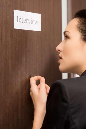 Mooie vrouw is kloppen op de deur. Zich klaar voor interview Stockfoto