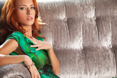 Red hair beauty. Beautiful young red hair woman sitting on the couch and looking at camera photo