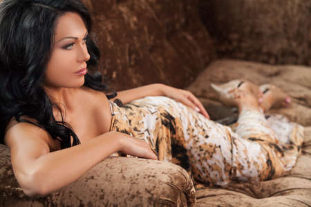 Beauty on the couch. Side view of beautiful young black hair woman lying on the couch and looking away Stock Photo - 23453740