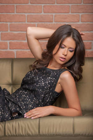 Beauty in gown wear. Beautiful young brown hair woman in formal dress lying on the couch and holding her hand in hair photo