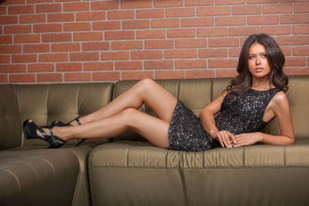 Beauty in gown wear. Beautiful young brown hair woman in formal dress lying on the couch and looking away photo
