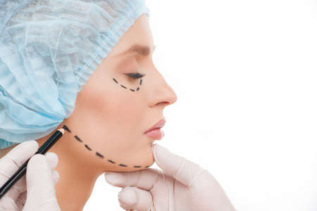 Preparing to plastic surgery. Side view of beautiful young woman in medical headwear and doctors hands marking her face with felt tip pen photo