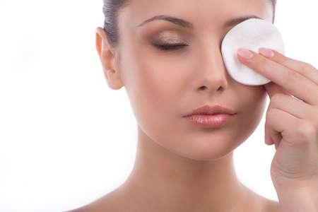 maquillage yeux: Suppression des yeux maquillage. Belle jeune femme en utilisant une boule de coton pour enlever le maquillage des yeux tout en isol� sur blanc