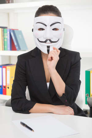 working place: Businesswoman in mask. Young woman in formalwear holding mask on her face while sitting at her working place Stock Photo