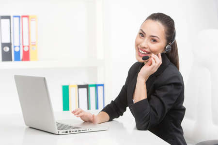 représentant du service à la clientèle au travail. Enthousiaste représentant du service à la clientèle travaillant à l'ordinateur et souriant Banque d'images