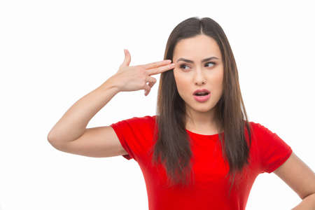 hand gun: Depressed woman. Displeased young woman holding her hand like a gun near head and looking away while isolated on white