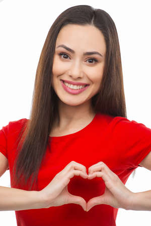 Heart shape. Beautiful young woman holding her hands in heart shape and smiling while isolated on white photo