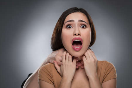 strangling: Choking. Portrait of shocked young woman with someones hands choking her while isolated on grey