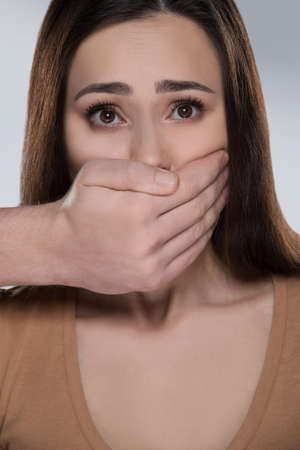 Shut up! Shocked young woman looking at camera while someone covering her mouth with hand