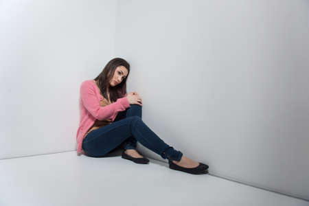 long depression: Loneliness. Depressed young woman sitting on the floor and leaning her head at the wall