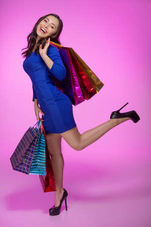Woman with shopping bags. Full length of cheerful young woman holding shopping bags and smiling at camera while standing isolated on colored background photo