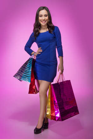 Woman with shopping bags. Full length of beautiful young woman holding shopping bags and smiling at camera while standing isolated on colored background photo