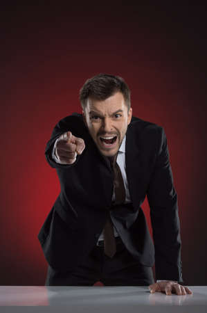 Angry boss. Furious young businessman pointing at camera and shouting while isolated on red photo
