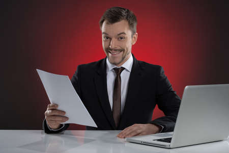 Happy businessman. Cheerful young businessman holding a paper and smiling while sitting at his working place isolated on red photo