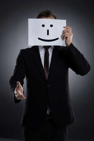 dishonesty: Smiling mask  Businessman holding a poster with smile on it in front of face and stretching out hand
