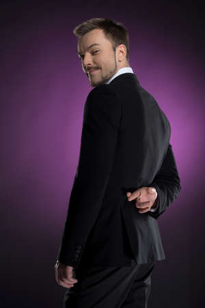 over the shoulder view: Dishonest businessman  Rear view of smiling businessman holding his fingers crossed and looking over shoulder while isolated on colored background Stock Photo