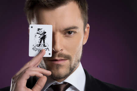 Joker man  Portrait of confident young businessman holding a joker card in front of his eye while isolated on colored background photo