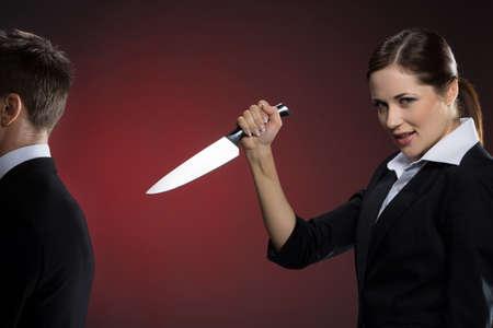 detras de: Socio incorrecto Sonriente mujer joven en ropa formal con un cuchillo cerca del hombre en traje de pie de nuevo a su